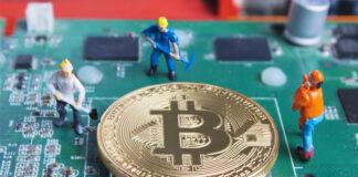 Miniature working man digging and mining Bitcoin on printed circ