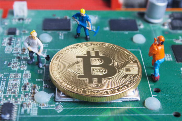 Miniature working man digging and mining Bitcoin on printed circ